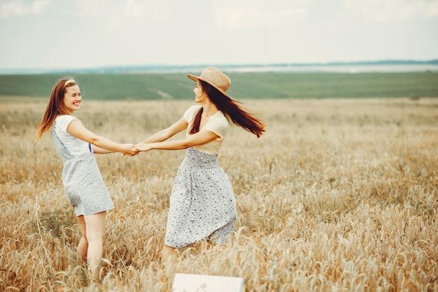 Mooie meisjes rusten uit in een veld Gratis Foto