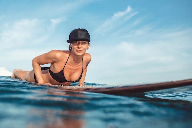 Mooie meisjes stellende zitting op een surfplank in de oceaan Gratis Foto