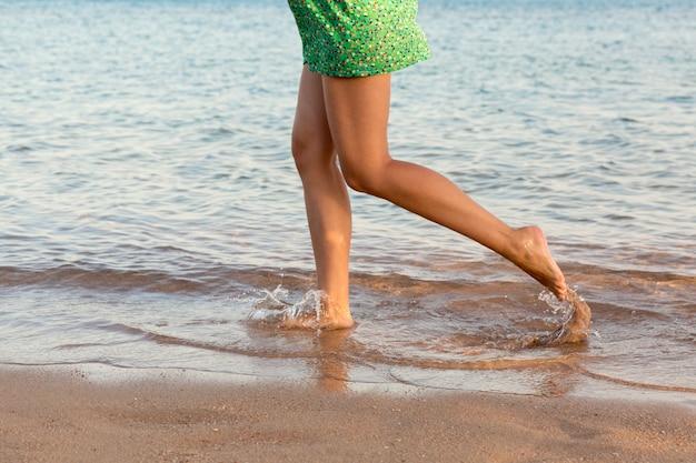 Mooie meisjesbenen die op het strand lopen. mooi meisje dat op water loopt Premium Foto