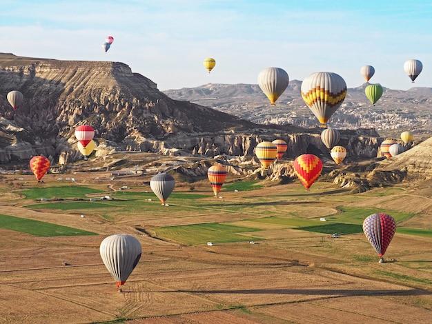 Mooie mening van kleurrijke hete luchtballons die over landschap in cappadocia, turkije vliegen. Premium Foto
