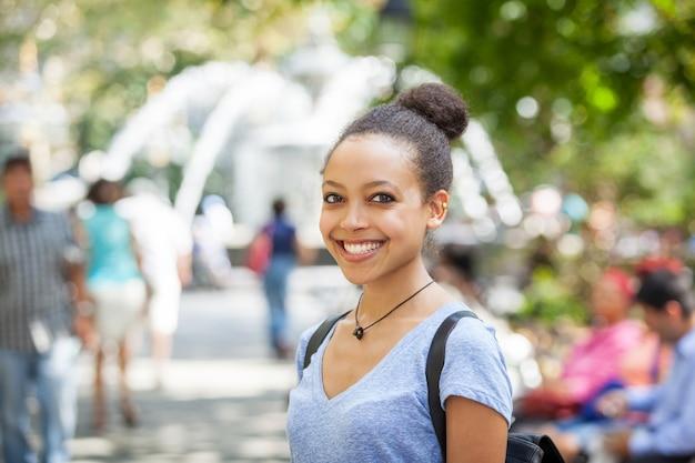 Mooie mixed-race jonge vrouw bij park, glimlachend portret Premium Foto
