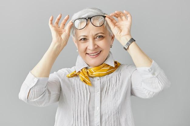 Mooie modieuze blanke vrouw gepensioneerde m / v met verziendheid die haar bril opstijgt om zich te concentreren op dichterbij gelegen objecten, breed glimlachend. oudere mensen, veroudering en visie probleemconcept Gratis Foto