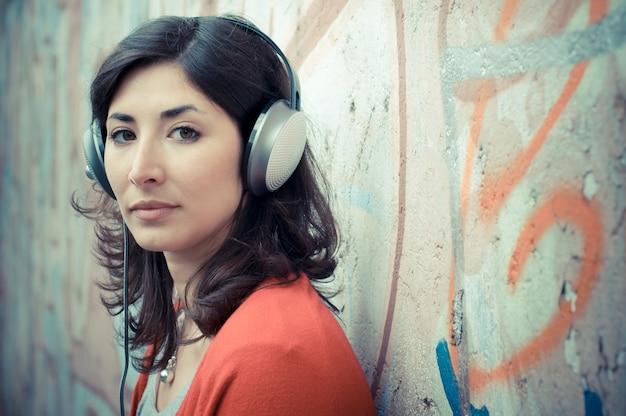 Mooie modieuze vrouw die aan muziek luistert Premium Foto