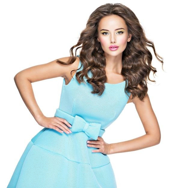 Mooie modieuze vrouw met lang haar in blauwe jurk. aantrekkelijke mannequin poseren op witte achtergrond. Gratis Foto