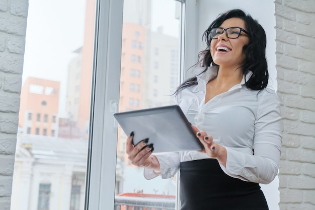 Mooie modieuze zakenvrouw met digitale tablet. Premium Foto