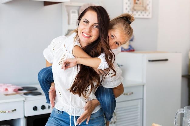 Mooie moeder die haar dochtertje houdt Gratis Foto