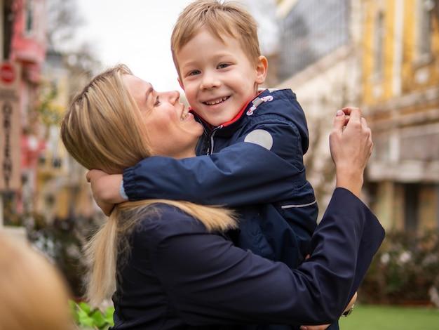 Mooie moeder die haar kind in openlucht houdt Gratis Foto