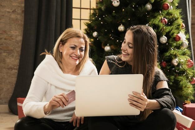 Mooie moeder en dochter met een laptop Gratis Foto
