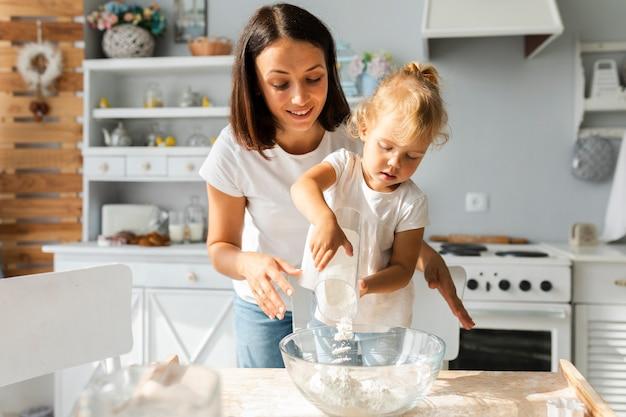 Mooie moeder en dochter samen koken Gratis Foto