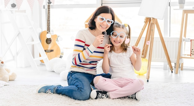 Mooie moeder en dochter spelen met stoklippen en glazen Premium Foto