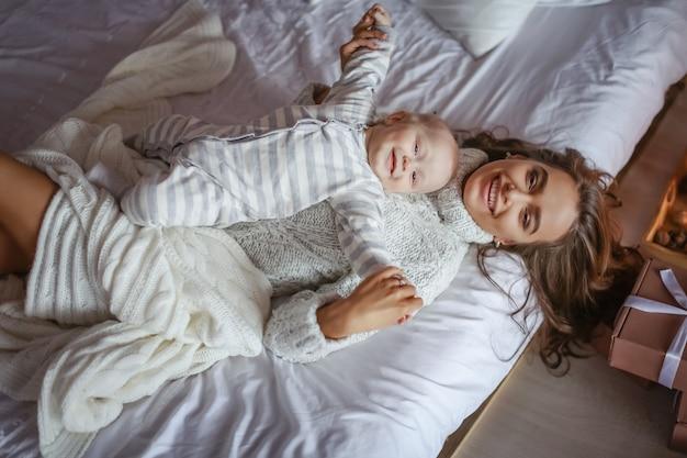 Mooie moeder met blauwe ogen en de baby liggend in de slaapkamer op het bed op het witte blad bovenaanzicht Premium Foto