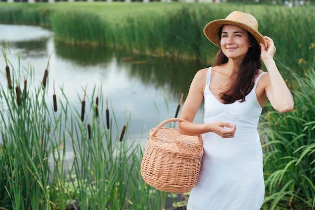 Mooie moeder poseren bij het meer met picknickmand Gratis Foto