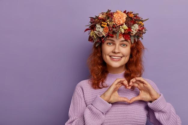 Mooie mooie gember meisje toont liefde teken, vormt hart met handen, heeft vriendelijke uitdrukking, draagt mooie herfstkrans op hoofd, gekleed in gebreide trui, geïsoleerd op paarse achtergrond Gratis Foto