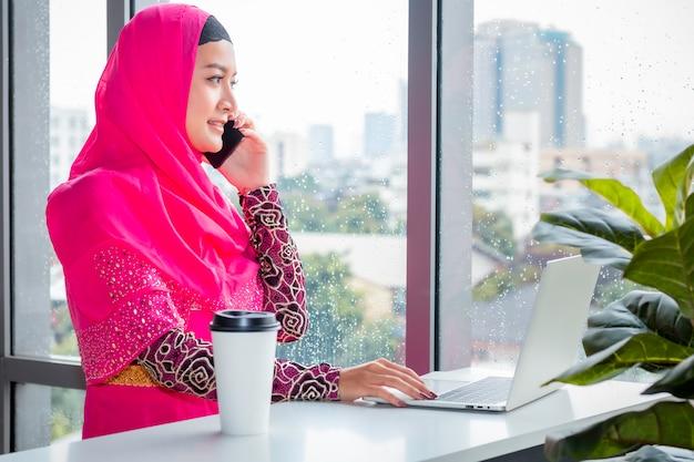 Mooie moslimvrouw die met telefoon op koffiewinkel spreekt. Premium Foto