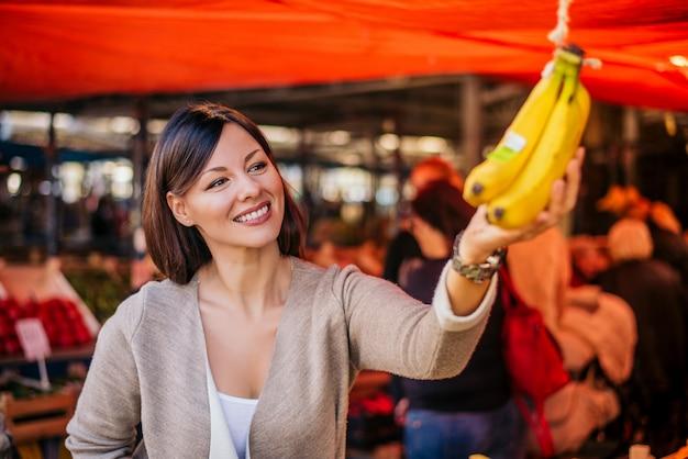 Mooie natuurlijke brunette het kopen bananen bij groene markt. Premium Foto