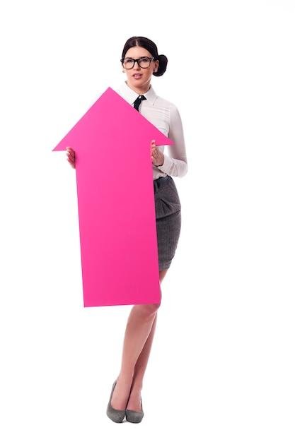 Mooie onderneemster die roze pijlteken houdt Gratis Foto