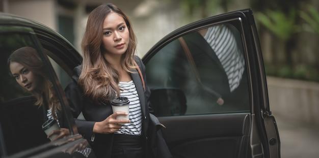 Mooie onderneemster die van de moderne luxeauto weggaat terwijl het houden van een koffiekop Premium Foto