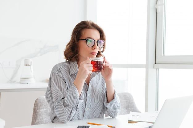 Mooie onderneemster in vrijetijdskleding die hete thee drinkt terwijl het zitten en het rusten na administratie thuis Gratis Foto