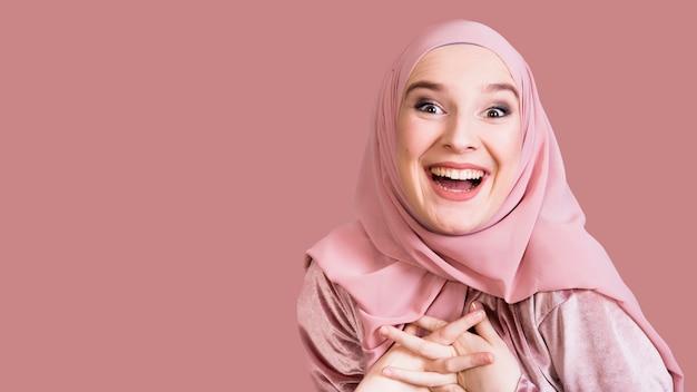 Mooie opgewekte vrouw die camera tegen gekleurde oppervlakte bekijkt Gratis Foto