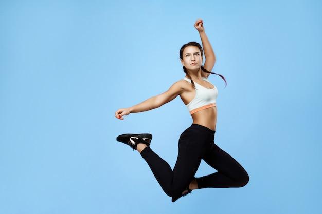 Mooie, opgewonden fitness vrouw in kleurrijke sportwear hoog springen Gratis Foto