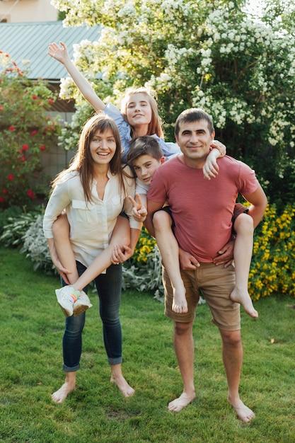 Mooie ouders die hun kinderen terug in park vervoeren Gratis Foto