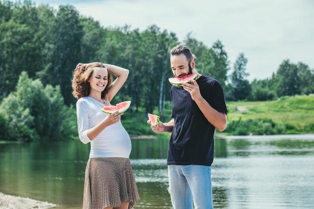 Mooie paar man en zwangere vrouw verliefd op een achtergrond Premium Foto