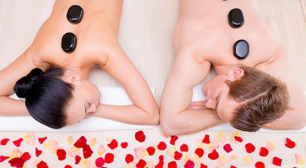 Mooie paar ontspannen in spa salon met hete stenen op lichaam. schoonheidsbehandeling therapie. Gratis Foto