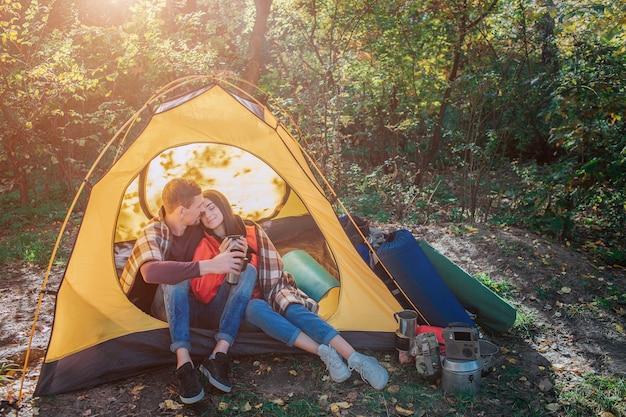 Mooie paar zittend in tent. ze leunt naar hem toe en houdt de ogen gesloten. haar schouders zijn bedekt met een deken. bebaarde man omhelst jonge vrouw. ze houden bekers vast. Premium Foto