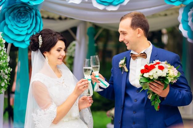 Mooie pasgetrouwde stel tijdens huwelijksceremonie rammelende glas Premium Foto