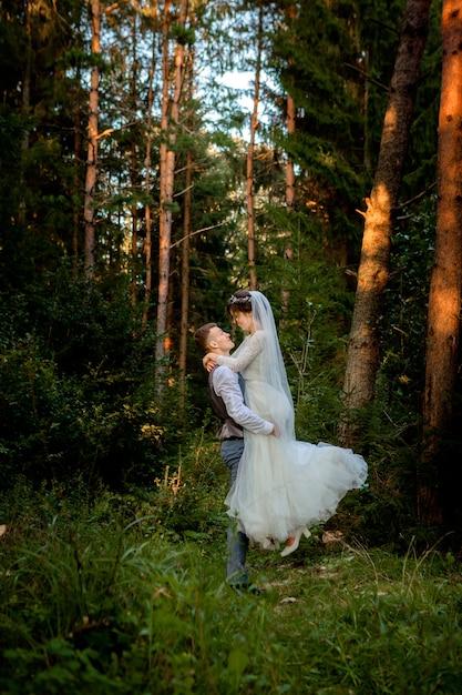 Mooie pasgetrouwden paar wandelen in het bos. pasgetrouwden. de bruid en de bruidegomholding dienen pijnboombos in, foto voor de dag van valentine Premium Foto