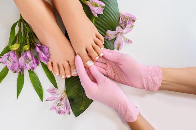 Mooie perfecte huid vrouwelijke benen voeten bovenaanzicht met tropische bloemen en groen palmblad Premium Foto