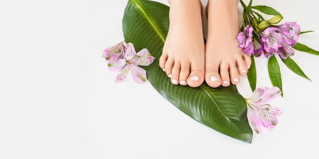 Mooie perfecte vrouwelijke huid benen voeten bovenaanzicht met tropische bloemen en groen palmblad Premium Foto