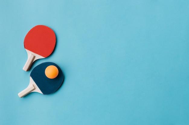 Mooie pingpongrackets met bal over blauwe ondergrondse Gratis Foto