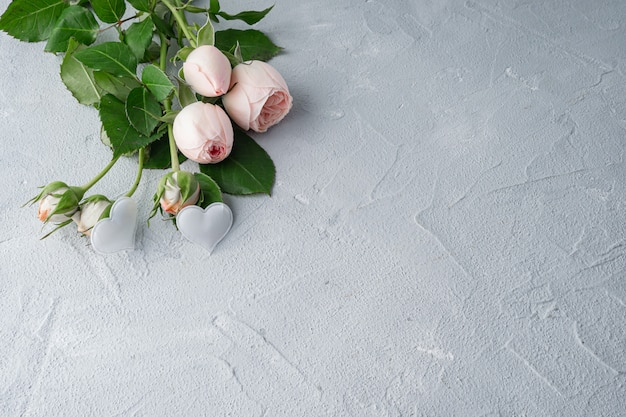 Mooie pioen bossige roze rozen en twee witte harten. valentijnsdag, het concept van liefde en loyaliteit. kopieer ruimte. Premium Foto