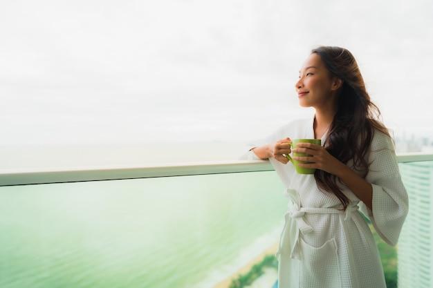 Mooie portret jonge aziatische vrouwen die koffiekop houden bij openluchtbalkon met overzeese oceaanmening Gratis Foto