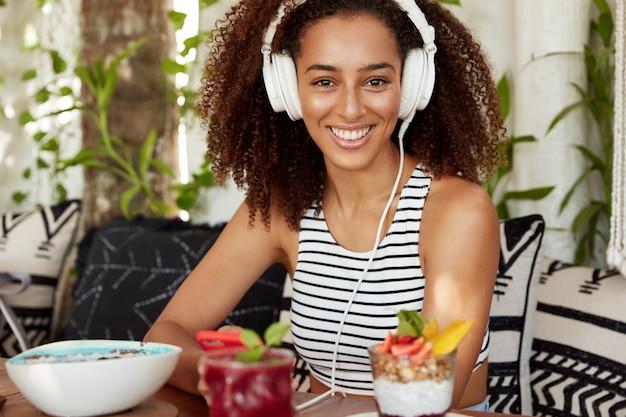 Mooie positieve afro-amerikaanse vrouw geniet van het luisteren naar muziek in de koptelefoon, besteedt vrije tijd in loft cafetaria met cocktail, heeft pauze na het werk, toont aangename glimlach. Gratis Foto