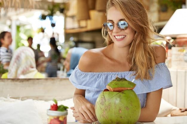 Mooie positieve jonge vrouw in zonnebril, geniet van kokos cocktail op terras, lacht aangenaam, verheugt zich met zomervakantie op tropische plek, exotische drank en dessert smaakt Gratis Foto