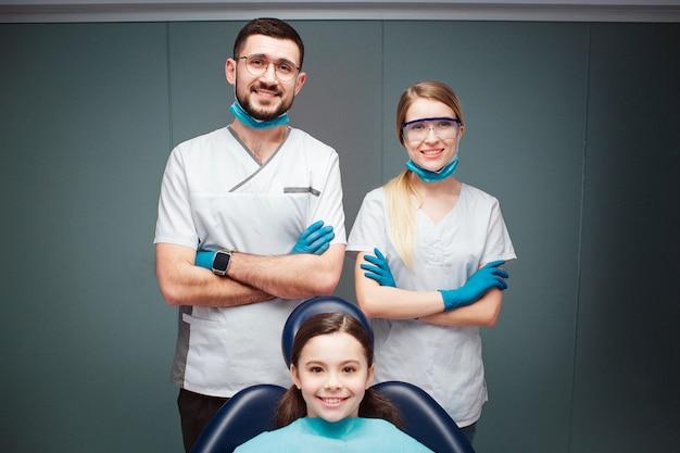 Mooie positieve mannelijke en vrouwelijke tandarts met meisje in tandartsstoel. ze zien er recht uit en glimlachen. volwassenen houden handen gekruist. geïsoleerd op groen. Premium Foto