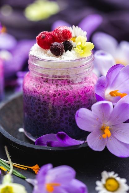 Mooie pot paarse veganistische smoothie overgoten met bessen, omgeven door lentebloemen Gratis Foto
