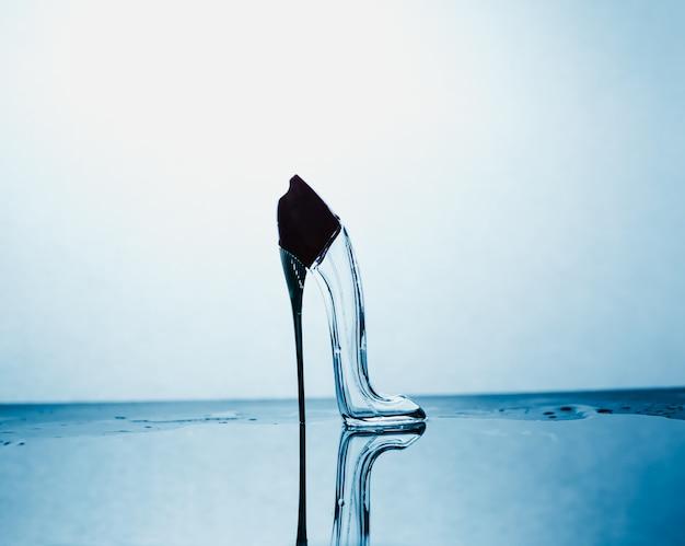 Mooie reflectie een glazen schoen op een blauwe abstracte achtergrond Premium Foto