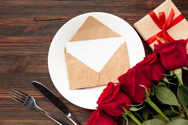 Mooie regeling voor het diner van de valentijnskaartendag op houten achtergrond met envelop Gratis Foto