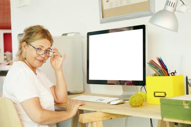 Mooie rijpe blonde vrouwelijke gepensioneerde die in bril achter computer zit Gratis Foto