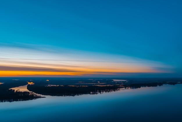 Mooie rivier met groot eiland met bomen onder predawnhemel. helder oranje streep in schilderachtige bewolkte hemel. vroege blauwe hemel weerspiegeld in water. kleurrijk ochtend atmosferisch beeld van majestueuze aard. Premium Foto