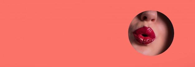 Mooie rode lippen die kus door gat op het leven koraaldocument achtergrond geven Premium Foto