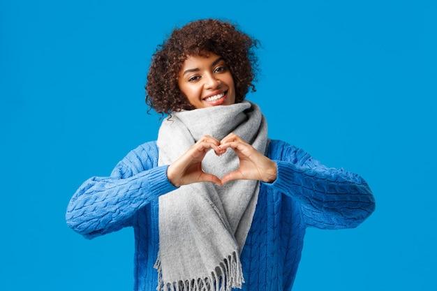 Mooie, romantische vrolijke afro-amerikaanse vriendin met een afro-kapsel, kantelend hoofd met hartteken, liefde en genegenheid belijdend, wintersjaal, trui dragend, staande over blauwe muur. Gratis Foto