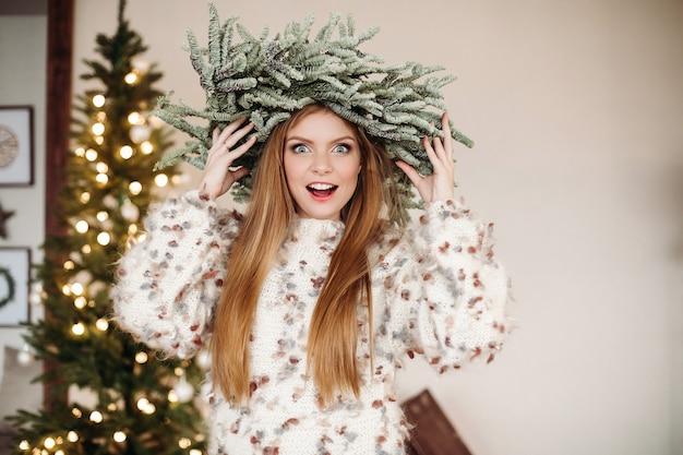Mooie roodharige draagt een prachtige kerstkrans op het hoofd en kijkt met verbazing naar de camera. Gratis Foto