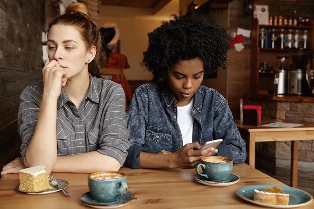 Mooie roodharige meid met bezorgde blik, zittend in café tijdens de lunch met haar internetverslaafde vriendin Gratis Foto