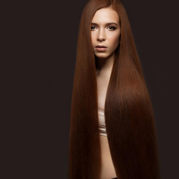 Mooie roodharige meid met een perfect glad haar en klassieke make-up. mooi gezicht. Premium Foto