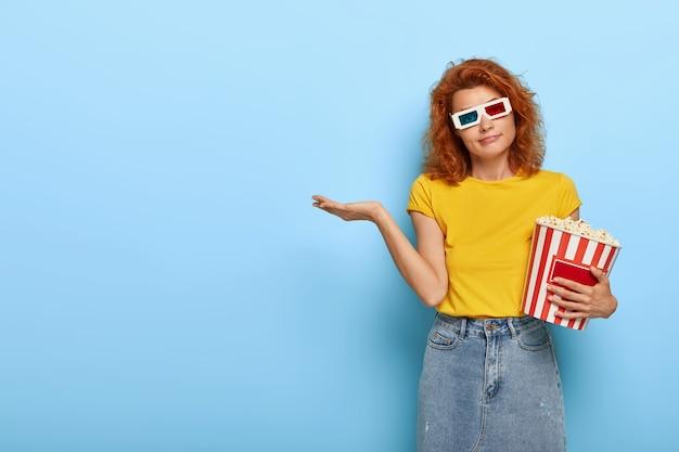 Mooie roodharige vrouw draagt virtuele bril, geel t-shirt en spijkerrok, houdt een mand met popcorn vast, komt in de bioscoop, heeft een twijfelachtige uitdrukking, twijfelt welke film ze moet kiezen om naar te kijken. Gratis Foto