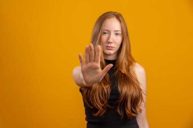 Mooie roodharigevrouw die zich over geïsoleerde gele muur met open hand bevinden die eindeteken met ernstige en zekere uitdrukking, verdedigingsgebaar doen. geen geweld meer tegen vrouwen. misbruik. Premium Foto